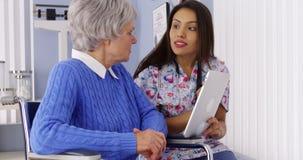 Hispanische Pflegekraft, die mit Tablette mit älterem Patienten spricht stockfotos