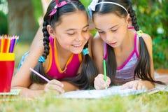 Hispanische Schwestern, die in Sommerpark zeichnen Lizenzfreie Stockbilder