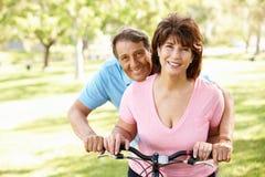 Hispanische senoir Paare mit dem Fahrrad, das an der Kamera lächelt Lizenzfreie Stockbilder