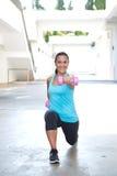 Hispanische Sportfrau, die Laufleinen mit dem rosa Dummkopf zwei, im Freien tut Stockfoto