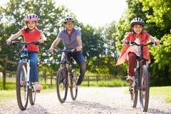 Hispanische Vater-And Children On-Zyklus-Fahrt Lizenzfreie Stockfotos