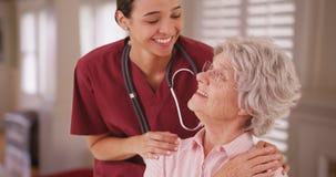 Hispanische weibliche Krankenschwester, die mit älterem Kaukasier schaut und lächelt stockfotografie