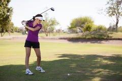 Hispanischer Brunette, der Golf spielt stockbilder