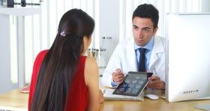 Hispanischer Doktor, der Gehirnröntgenstrahlen mit Patienten wiederholt Stockbilder