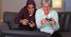 Hispanischer Enkel und Großmutter, die Videospiele spielt Lizenzfreie Stockfotografie