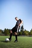 Hispanischer Fußball- oder Fußballspieler, der eine Kugel tritt Lizenzfreie Stockfotos