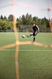 Hispanischer Fußball- oder Fußballspieler, der eine Kugel tritt Lizenzfreies Stockbild