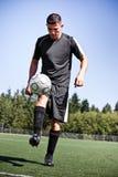 Hispanischer Fußball- oder Fußballspieler, der eine Kugel tritt Stockfoto