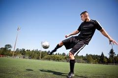 Hispanischer Fußball- oder Fußballspieler, der eine Kugel tritt Lizenzfreie Stockfotografie