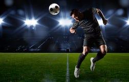 Hispanischer Fußball-Spieler, der den Ball vorangeht Stockbild