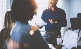 Hispanischer Geschäftsmann, der Papierhände und -c$lächeln hält Junges Team von den Mitarbeitern, die große Geschäftsdiskussion i Lizenzfreies Stockfoto