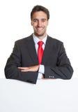 Hispanischer Geschäftsmann mit Klage und weißes Brett Lizenzfreie Stockfotos