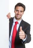 Hispanischer Geschäftsmann mit Klage und weißes Brett, das sich Daumen zeigt Stockbilder