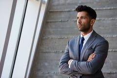 Hispanischer Geschäftsmann Standing Against Wall im modernen Büro lizenzfreie stockfotos