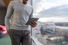 Hispanischer Geschäftsmann, der Tablet-Computer-Stand im vorderen panoramischen Fenster-Geschäftsmann In Coworking Center verwend Stockbild