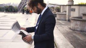 Hispanischer Journalist nah an Eiffelturmlesezeitung und Betrachten der Uhr in der Zeitlupe stock video footage