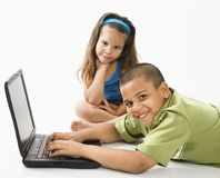 Hispanischer Junge auf Laptop mit Schwester. stockbilder