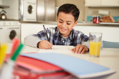 Hispanischer Junge, der bei Tisch Hausarbeit tut Stockfoto