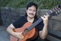 Hispanischer Mann, der draußen Akustikgitarre spielt Stockbild