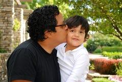 Hispanischer Mann, der draußen seinen entzückenden Sohn küßt Lizenzfreie Stockfotos