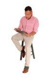 Hispanischer Mann, der mit Tabletten-PC sitzt Stockfotografie
