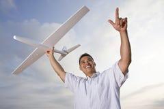 Hispanischer Mann, der vorbildliches Flugzeug obenliegend anhält Stockbild