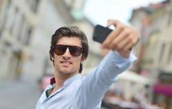 Hispanischer Mann des jungen modernen Hippies mit der Sonnenbrille, die ein selfie nimmt Stockfotografie