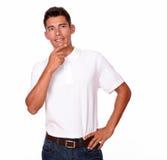 Hispanischer Mann im weißen T-Shirt, das reflektierend schaut. lizenzfreie stockbilder