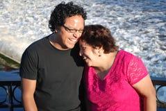 Hispanischer Mann und seine Mutter, die durch einen Fluss lacht Stockfoto