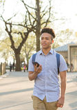 Hispanischer Student mit dem gelockten Haar geht auf Baum gezeichneten Campus Lizenzfreie Stockfotos