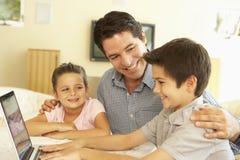 Hispanischer Vater-And Children Using-Computer zu Hause Lizenzfreie Stockfotos