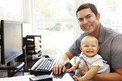 Hispanischer Vater mit dem Baby, das im Innenministerium arbeitet Lizenzfreies Stockfoto