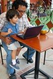 Hispanischer Vater und Sohn auf Laptop Stockbilder