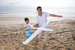 Hispanischer Vati, Mädchen, das mit Spielzeugflugzeug auf Strand spielt Stockbilder