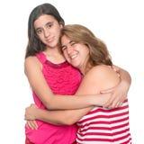 Hispanisches jugendlich Mädchen, das ihre Mutter und Lächeln umarmt Lizenzfreie Stockbilder