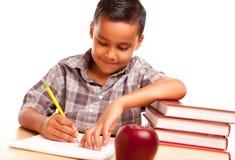 Hispanisches Jungen-Schreiben mit Büchern, Apple Lizenzfreies Stockfoto