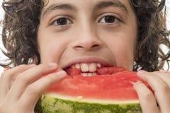 Hispanisches Kind, das neue Wassermelonenscheibe isst Lizenzfreie Stockfotos