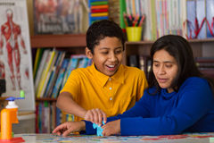 Hispanisches Kind, das Puzzlespiel mit Mutter abschließt Stockfotos