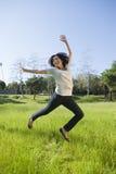 Hispanisches Mädchen, das auf einem grasartigen Gebiet springt   Stockbild