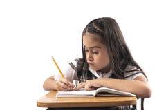 Hispanisches Mädchen, das in der Schule schreibt lizenzfreies stockfoto