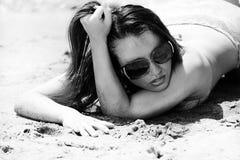 Hispanisches Mädchen im Badeanzug, der auf dem Sand liegt Stockbild