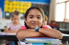 Hispanisches Mädchen mit dem Kinn auf Büchern lizenzfreies stockfoto