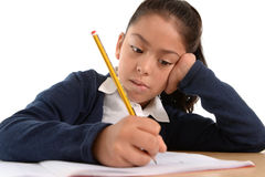 Hispanisches weibliches Kind, das sorgfältig Hausarbeit mit Bleistift mit starkem Gesicht schreibt Stockbilder