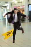 Hispanoc-Geschäftsmann Falling auf nassem Boden Stockfotografie
