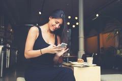 年轻hispter女孩在咖啡店观看在手机whille的滑稽的录影坐 免版税库存图片