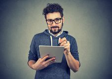 Hispter mężczyzna trzyma pastylki pióro i komputer patrzeje kamerę w szkłach fotografia royalty free