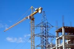 Hissa tornkranen och överkanten av industribyggnad Arkivfoto