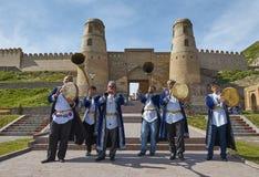 HISSAR, TAJIKISTAN-MARCH 15,2016: Los músicos en nacional visten a las huéspedes agradables a la fortaleza de Hissar Fotografía de archivo libre de regalías