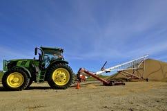 Hissen för det John Deere traktorröret överför sojabönor royaltyfri fotografi