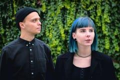 História de amor gótico dos pares Homem e menina azul do cabelo na roupa preta no fundo de Green River Fotografia de Stock